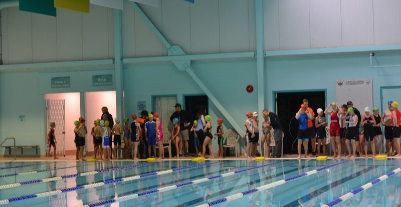 Athletes stand at the poolside waiting to start.