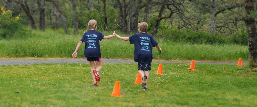 A racer shares a high five with an athlete that is already done at the youth triathlon in the West Shore.
