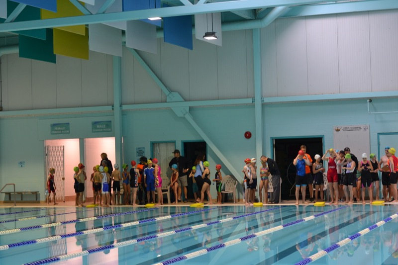 Athletes and volunteers line up along the wall at the gym to start.