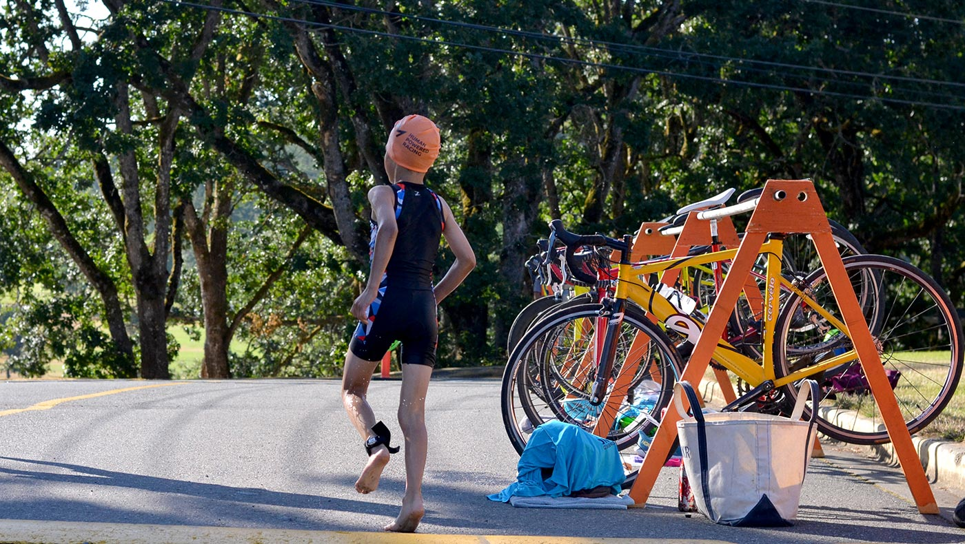 A young racer runs into the transition zone to get ready for the bike!